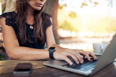 44972543 - young woman wearing smartwatch using laptop computer. female working on laptop in an outdoor cafe.